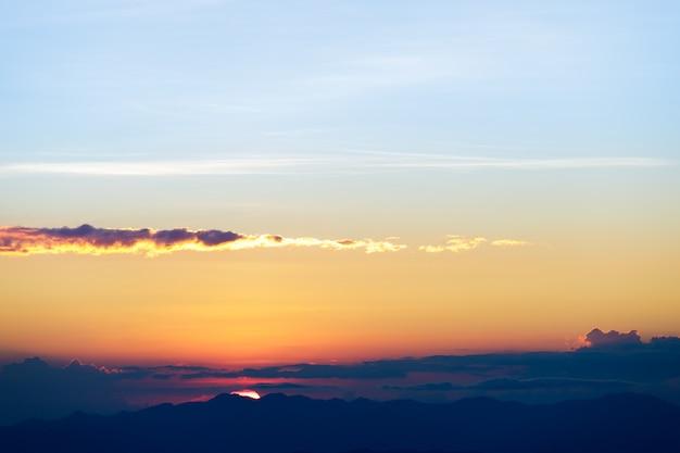 Tramonto naturale alba. cielo drammatico luminoso e terreno scuro. paesaggio di campagna sotto il cielo colorato scenico