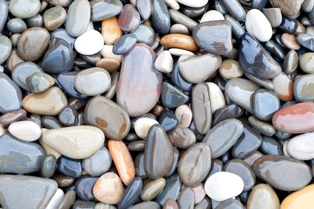 Sfondo texture naturale, pietre di mare colorate in acqua, vista dall'alto