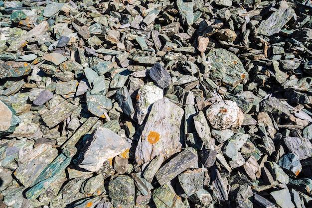 La struttura naturale della montagna dei massi friabili si chiude su. sfondo dettagliato di pietre grigie con muschio arancione.