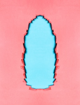 Naturale di carta ruvida rosa strappata su sfondo di colore blu.