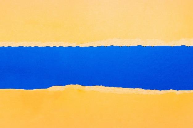 Documento strutturato giallo strappato naturale su colore blu.