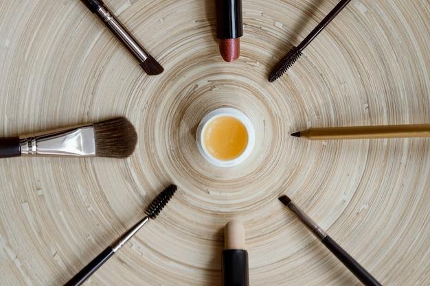 Trucco vegano naturale su uno sfondo di legno pennelli per mascara matita lucida per rossetto lay piatto di cosme