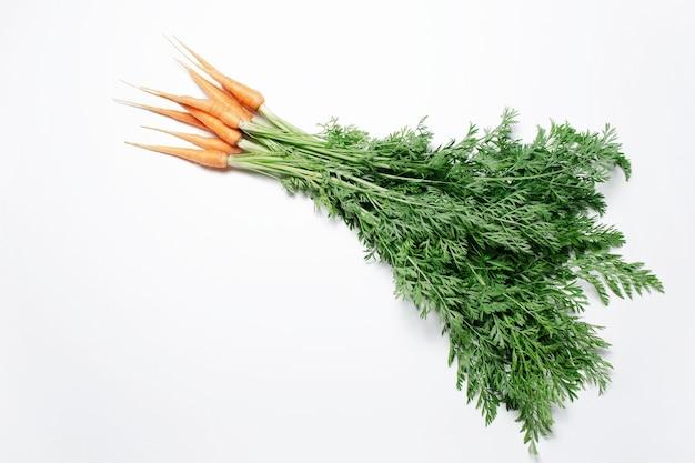 Vista naturale di carote fresche su sfondo bianco.