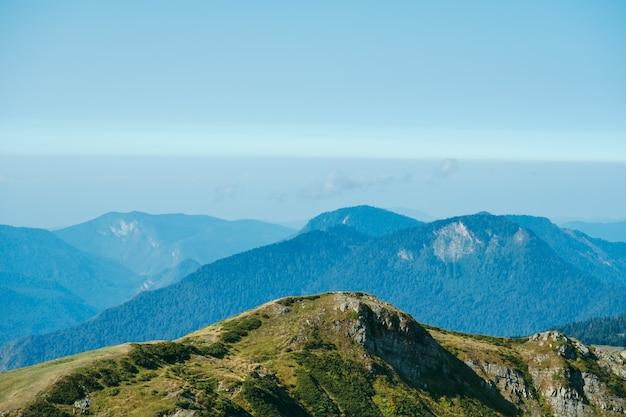 Carta da parati naturale con alte montagne nella nebbia e collina verde