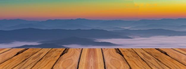Tavole di legno naturale e sfondo di montagna e nebbia