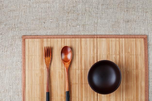 Piatto, cucchiaio e forchetta in legno naturale su supporto di bambù. concetto di artigianato alimentare asiatico. vista dall'alto