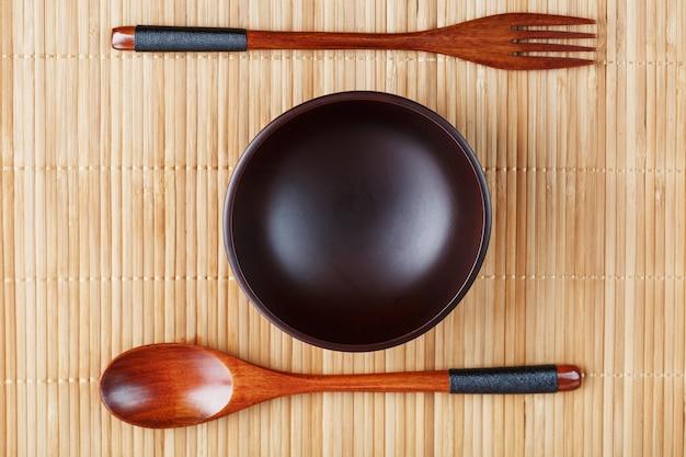 Piatto, cucchiaio e forchetta in legno naturale su supporto di bambù.