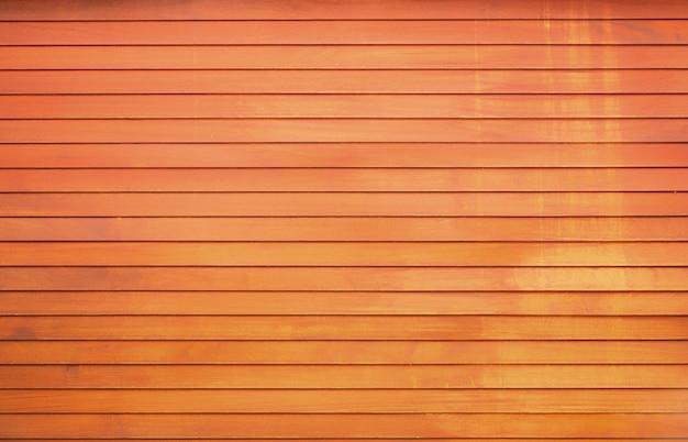 Parete in legno naturale, pannelli dipinti di arancione con riflessi gialli. texture di sfondo di alta qualità