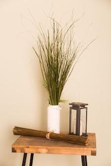 Tavolo in legno naturale in stile moderno nei toni del beige con un vaso di fiori secchi e una lampada in rame.