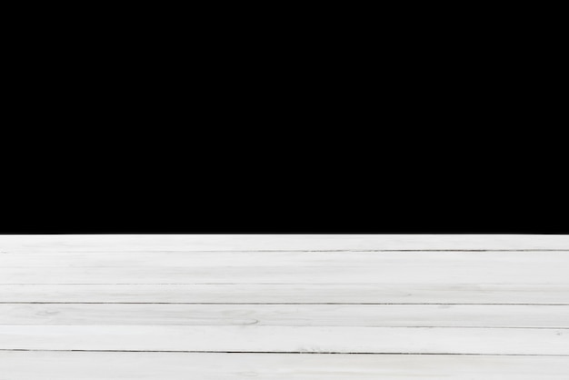 Tavolo vecchio vuoto testurizzato in legno naturale colore grigio chiaro su sfondo nero. può essere utilizzato per la tua creatività o per montare i tuoi prodotti. messa a fuoco utilizzata per creare una profondità di campo completa.