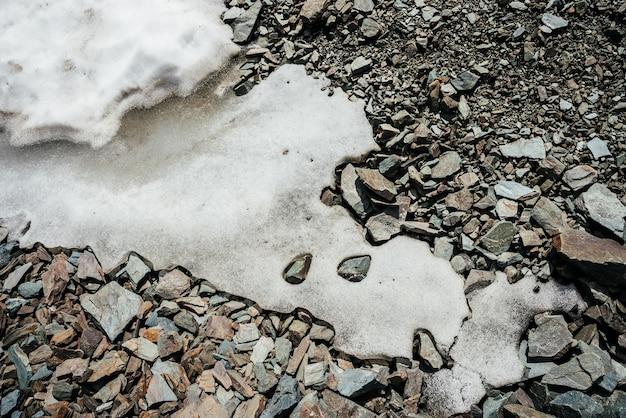 Sullo sfondo della natura della neve sul mucchio caotico di pietre.