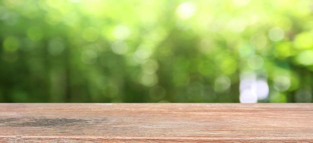Fondo della natura, esposizione di legno della tavola sopra il giardino di verde della sfuocatura