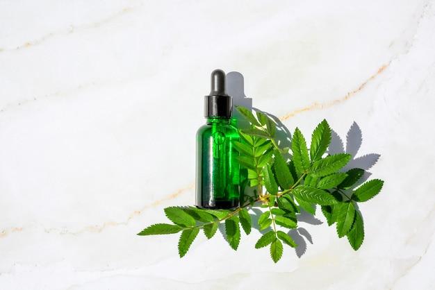 Cosmetici naturali in bottiglia di vetro con pipetta e fiori