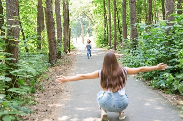 Natura, famiglia, concetto di persone - adorabile ragazzino ragazza e giovane donna nella bellissima foresta