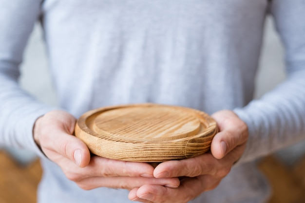 Concetto di protezione della natura. vassoio in legno nelle mani dell'uomo.
