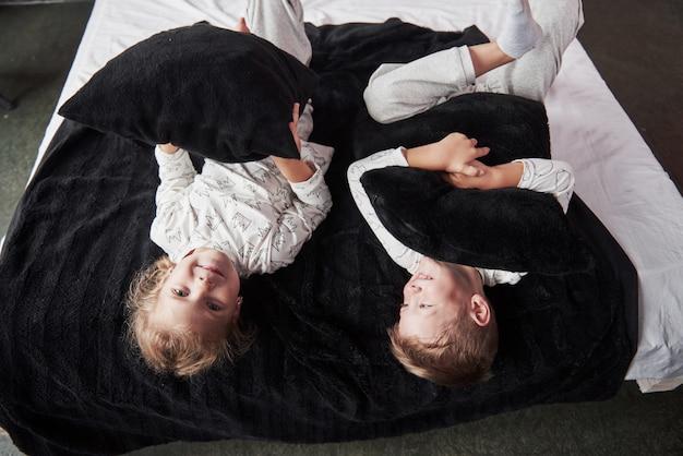 Bambini cattivi ragazzino e ragazza hanno organizzato una lotta con i cuscini sul letto in camera da letto. a loro piace quel tipo di gioco