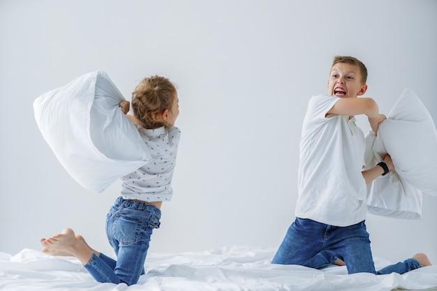 Gemelli cattivi amichevoli che combattono con i cuscini sul letto