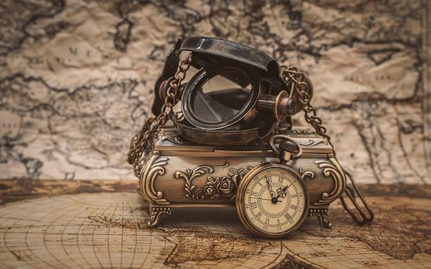 Lente d'ingrandimento nautica e collana di orologi sulla mappa