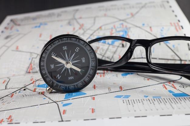 Bussola di navigazione accanto a mappa e occhiali