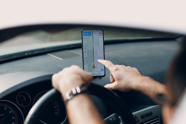 Navigatore nel pendolare del trasporto del veicolo dell'automobile. autista che utilizza l'app del navigatore del telefono cellulare durante la guida dell'auto