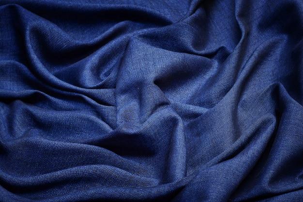 Vista superiore del fondo di struttura del tessuto blu navy. sfondo bianco panno sgualcito