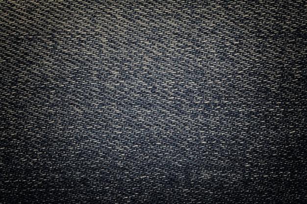Primo piano del fondo della tessile del denim squallido blu navy. macro tessuto strutturato