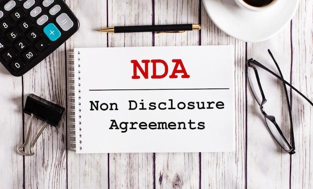 Gli accordi di non divulgazione sono scritti in un blocco note bianco vicino a una calcolatrice, caffè, occhiali e una penna. concetto di affari