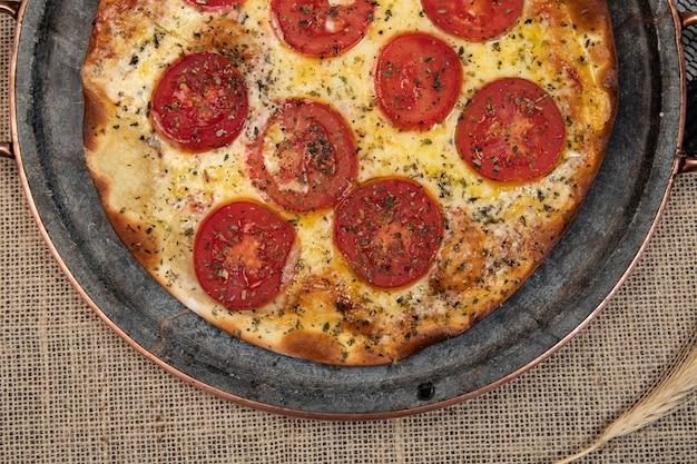 Pizza napoletana brasiliana con mozzarella e fette di pomodoro con origano, vista dall'alto