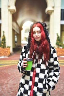 Vicino al ritratto di una ragazza adolescente con i capelli rossi in vestiti caldi in piedi fuori in una giornata fredda con una tazza di caffè in mano e guarda nella telecamera.