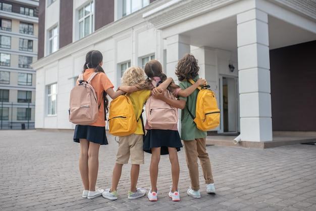 Vicino all'edificio scolastico. scolari in piedi nel cortile della scuola e guardando l'edificio scolastico