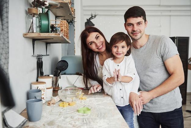 Vicino al tavolo in cucina. famiglia carina in posa per la foto.