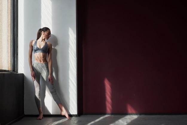 Vicino alla finestra. la ragazza con un buon tipo di corpo fitness ha esercizi nella stanza spaziosa