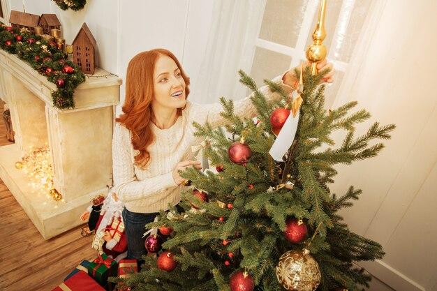 Quasi fatto. vista dall'alto su una donna rossa gioiosa che sorride mentre si trova accanto a un albero di natale e lo decora da solo.