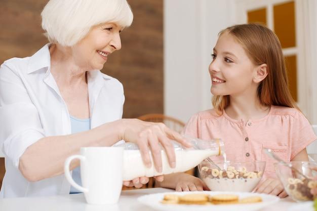 Nonna gentile e attenta che versa il latte nei cereali mentre si gusta la colazione con la nipote