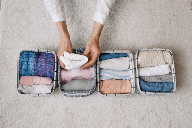 Una casalinga ordinata mette le cose in un contenitore per la biancheria durante la pulizia generale con l'aiuto di un moderno sistema di stoccaggio. vista dall'alto il concetto di un'organizzazione bella e confortevole