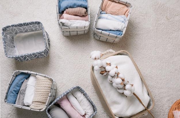 Vestiti ben piegati in scatole organizer aperte, vista dall'alto. un ramo di cotone. il concetto di pulizia