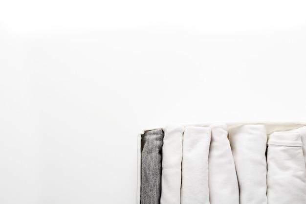 Vestiti bianchi e grigi ordinatamente piegati in un contenitore per un guardaroba o un viaggio sul bianco. ordina nel guardaroba.