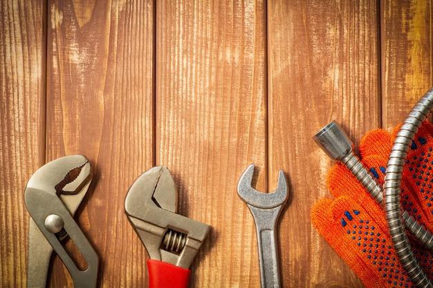 Set necessario di strumenti per idraulici su uno sfondo di legno vintage