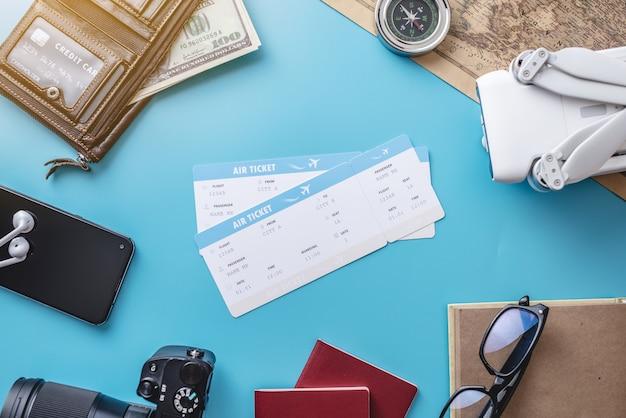 Cose necessarie per il volo in vacanza. biglietti aerei, passaporto, telefono, carta di credito, quadricottero drone, fotocamera su sfondo blu