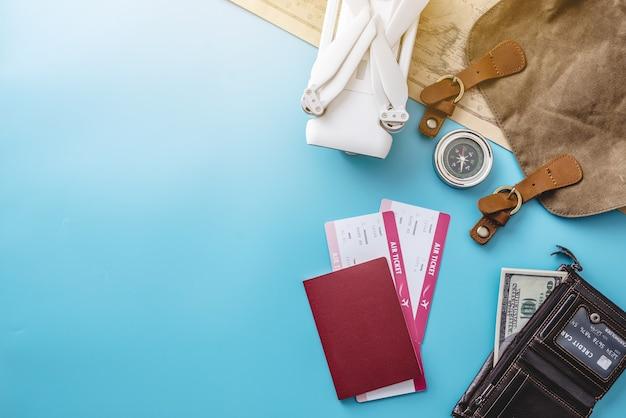 Cose necessarie per il volo in vacanza. biglietti aerei, passaporto, telefono, quadricottero drone, fotocamera su sfondo blu
