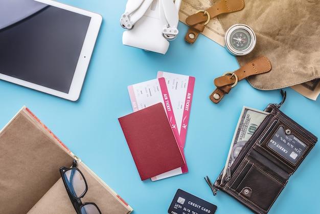 Cose necessarie per il volo in vacanza. biglietti aerei, passaporto, tablet, quadricottero drone, fotocamera su sfondo blu