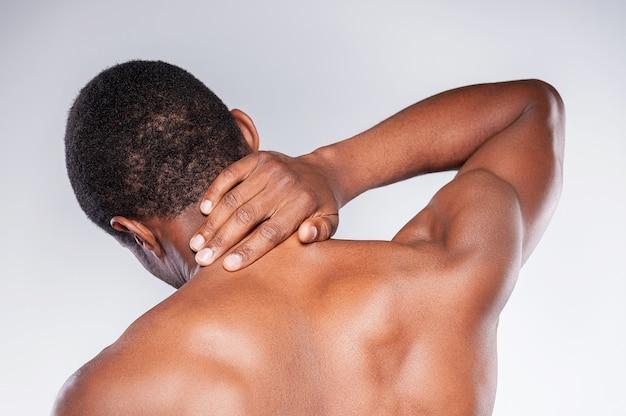 Dolore al collo. vista posteriore di un giovane africano senza camicia che si tocca il collo mentre sta in piedi su uno sfondo grigio