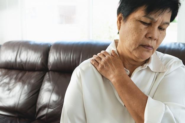 Dolore al collo e alla spalla, anziana che soffre di lesioni al collo e alla spalla, concetto di problema di salute