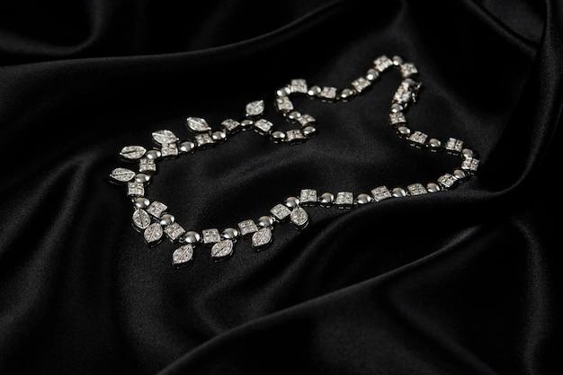 Collana con diamanti su sfondo nero con copia spazio. collana da donna in platino con pietre preziose, primo piano. eleganti gioielli femminili