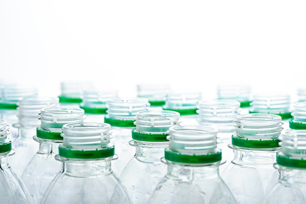 Colli di bottiglie di plastica senza tappi su sfondo bianco. produzione del concetto di bottiglie di plastica