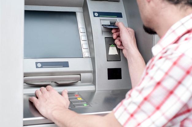 Ho bisogno di un po 'di denaro. vista dall'alto di un uomo che usa la sua carta di credito al bancomat