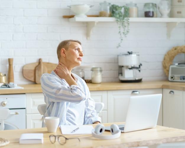 Ho bisogno di un po' di riposo, una donna matura stanca che si massaggia il collo mentre lavora o studia sul laptop online su