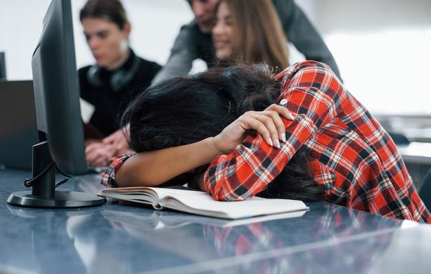 Hai bisogno di dormire. gruppo di giovani in abiti casual che lavorano nell'ufficio moderno.