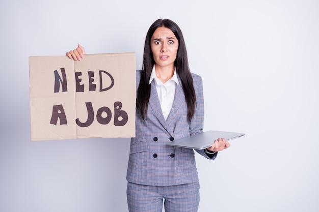 Bisogno di lavoro. foto di attraente licenziata triste terrorizzata signora tenere cartone cartellone cercare lavoro freelance offerta proposta tenere netbook gadget abbigliamento formale abito scozzese isolato colore grigio sfondo