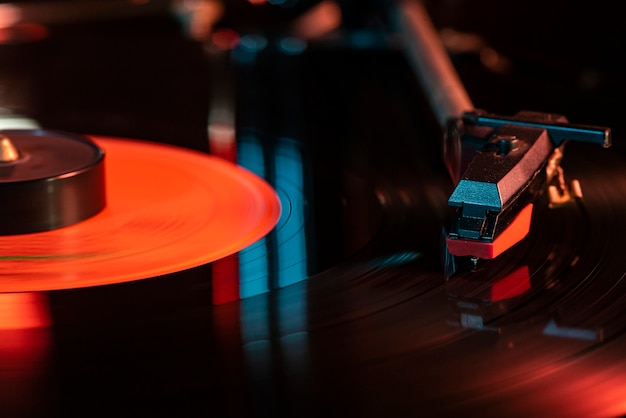 Dettaglio dell'ago sul disco in vinile sul giradischi, immagine in condizioni di scarsa illuminazione con riflesso